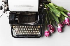 Estilo antigo retro da máquina da máquina de escrever pela flor das tulipas imagem de stock