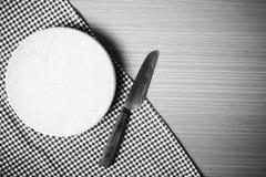 Estilo blanco y negro del tono del color del cuchillo y de la tabla de cortar Imagen de archivo libre de regalías