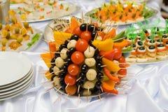 Estilo de abastecimiento de la comida fría - tomates y aceitunas Imagen de archivo libre de regalías