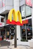 Estilo de Dicut de la muestra del logotipo del ` s de McDonald en el pilar delante del restaurante del ` s de McDonald en la plaz imagen de archivo