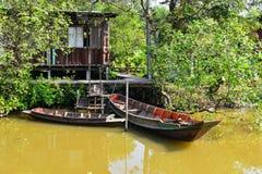 Estilo de la casa de campo de Tailandia en el jardín al lado del río con los barcos Fotografía de archivo libre de regalías