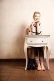 Estilo de la vendimia Muchacha descalza que se sienta en el escritorio retro Foto de archivo libre de regalías