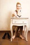 Estilo de la vendimia Muchacha descalza que se sienta en el escritorio retro Imagen de archivo libre de regalías