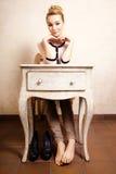 Estilo de la vendimia Muchacha descalza que se sienta en el escritorio retro Fotografía de archivo libre de regalías