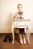 Estilo de la vendimia Muchacha descalza que se sienta en el escritorio retro Fotografía de archivo