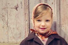 Estilo de la vendimia Pequeña muchacha linda en el fondo del doo viejo Imagen de archivo