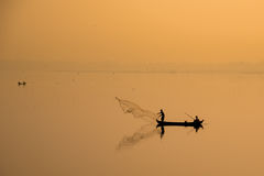 Estilo de vida asiático: pescador que lanza una red en el lago en la salida del sol, rural en Tailandia Fotografía de archivo libre de regalías