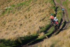 Estilo de vida ativo de biking de montanha dos pares através dos montes de Victoria de Christchurch foto de stock royalty free