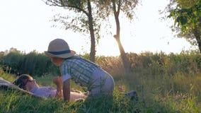 Estilo de vida do divertimento, jogo de crianças junto no campo no por do sol durante férias de verão video estoque