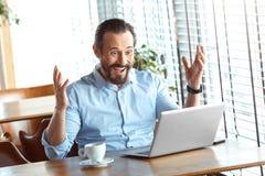 Estilo de vida do negócio Comerciante que senta-se no café com o café que olha o sorriso das mãos do portátil de lado surpreendid imagens de stock royalty free