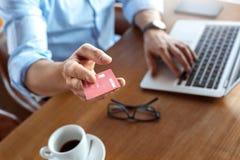 Estilo de vida do negócio Comerciante que senta-se no café com café usando o portátil que dá o cartão de crédito ao close-up da c imagens de stock royalty free