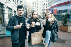 Estilo de vida e conceito dos povos: duas meninas e indiv?duo que comem o fast food na rua da cidade junto que tem o divertimento imagem de stock royalty free