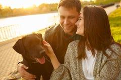 Estilo de vida, família feliz que descansa no piquenique no parque com um cão Imagens de Stock