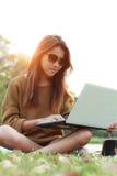 Estilo de vida moderno exterior do laptop do portátil do uso do sorriso da menina Fotografia de Stock Royalty Free