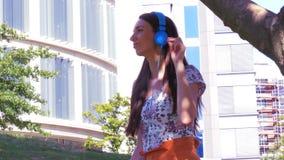 Estilo de vida moderno - uma mulher alegre escuta a música e relaxa no parque da cidade durante o fim de semana video estoque