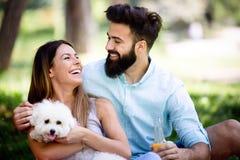 Estilo de vida, par feliz que descansa em um piquenique no parque com um cão imagem de stock royalty free