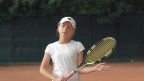 Estilo de vida saudável ambicioso novo, retrato da menina do jogador de tênis com a raquete nas mãos na corte vermelha fora vídeos de arquivo