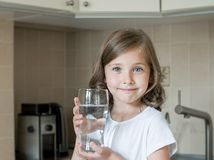 Estilo de vida saud?vel Retrato da moça de sorriso feliz com vidro Criança que bebe a água fresca na cozinha em casa sa?de imagens de stock royalty free