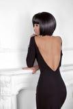 Estilo de Vogue. Mujer de la belleza de la moda en el vestido sexy que muestra detrás. Br Imagen de archivo