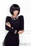 Estilo de Vogue. Mujer de la belleza de la moda en vestido del negro sexy.  imagen de archivo