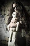Estilo del horror tirado: muchacha triste extraña con la muñeca del moppet en manos fotografía de archivo