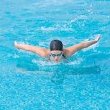 Estilo del movimiento de mariposa de la natación de la chica joven Imágenes de archivo libres de regalías