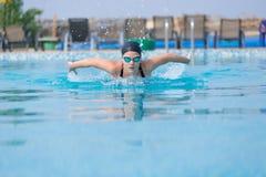 Estilo del movimiento de mariposa de la natación de la chica joven Imagen de archivo libre de regalías