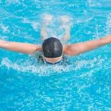 Estilo del movimiento de mariposa de la natación de la chica joven Foto de archivo libre de regalías