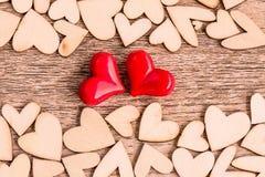 Estilo del vintage de dos corazones rojos con los corazones de madera en un de madera Imagenes de archivo