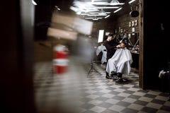 Estilo do ` s dos homens O barbeiro da forma faz um penteado à moda para um homem preto-de cabelo que senta-se na poltrona no à m foto de stock