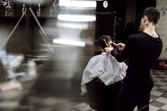 Estilo do ` s dos homens O barbeiro da forma faz um penteado à moda para um homem preto-de cabelo que senta-se na poltrona no à m imagem de stock