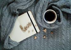 Estilo escandinavo, una taza de café con un cuaderno y corazones en una textura hecha punto, espacio para el texto fotografía de archivo
