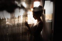 Estilo hermoso de la novia Casarse el soporte de la muchacha en vestido que se casa de lujo cerca de la ventana fotos de archivo libres de regalías