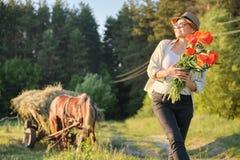 Estilo rústico, mulher feliz madura no chapéu com os ramalhetes de flores das papoilas que anda ao longo da estrada secundária imagem de stock
