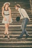 Estilo retro de los pares cariñosos que liga en las escaleras Foto de archivo libre de regalías