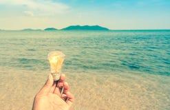 Estilo retro do homem que guarda a ampola na praia com montanha foto de stock