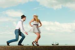 Estilo retro dos pares loving que data na costa de mar Foto de Stock