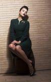 Estilo retro. Menina Pin-acima que senta-se no vestido verde no tambor sobre a parede de Brown do tijolo Fotografia de Stock Royalty Free