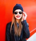 Estilo sonriente del negro de la roca de la moda de la mujer rubia del retrato que lleva sobre rojo Imagenes de archivo