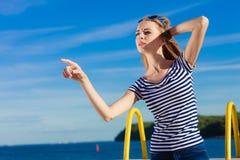 Estilo sport de la mujer que señala en fondo del cielo Fotos de archivo