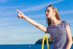 Estilo sport de la mujer que señala en fondo del cielo Imagen de archivo libre de regalías