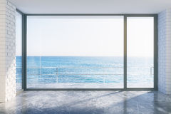Estilo vacío del desván con el piso concreto y la vista al mar Fotografía de archivo