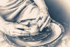 Estilo velho do vintage o oleiro da pessoa faz o potenciômetro de terra em uma roda do ` s do oleiro foto de stock