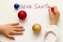 Estimado Papá Noel - desee la tarjeta escrita por el niño a Santa Claus en la Navidad El ` s del niño da la letra de la escritura fotografía de archivo libre de regalías