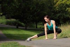 Estiramento atlético do warm up da mulher do ajuste bonito Imagens de Stock