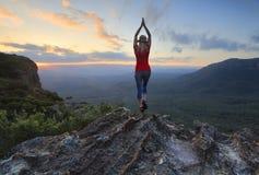 Estiramento fêmea da aptidão à cena do vale da parte superior da montanha do céu imagem de stock royalty free
