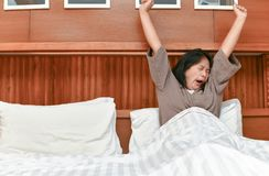 Estiramento novo da esposa e bocejo na cama fotografia de stock