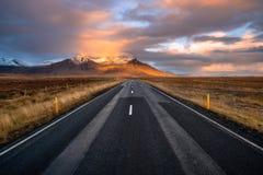 Estiramento reto de uma estrada cênico em Islândia no por do sol imagem de stock