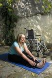 Estiramentos ao lado da cadeira de rodas - vertical da mulher Imagem de Stock