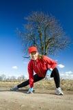 Estiramentos da mulher após o corredor do país transversal Fotografia de Stock Royalty Free